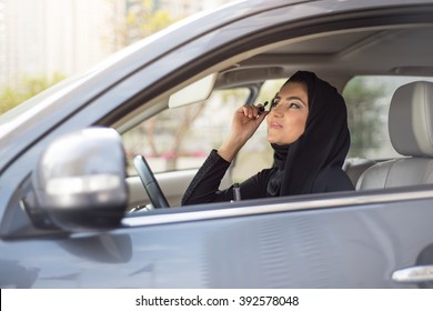 Middle Eastern Woman Sitting in a Car on a Driver's Place and Applying Make-Up
