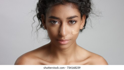 middle eastern young woman in studio with a foundation on cheek closeup