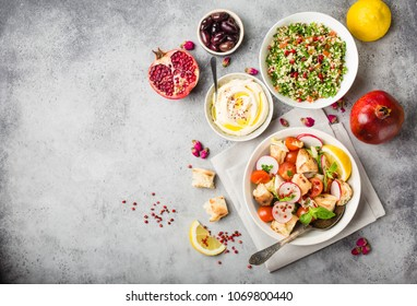 Middle eastern/arabic dishes and meze, concrete rustic background. Space for text. Fattoush bread salad, tabbouleh, hummus, olives, pita. Halal food. Lebanese cuisine. Middle eastern dinner. Top view