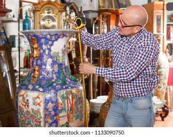Middle elderly man working in antique store, measuring vintage vase with tape rule