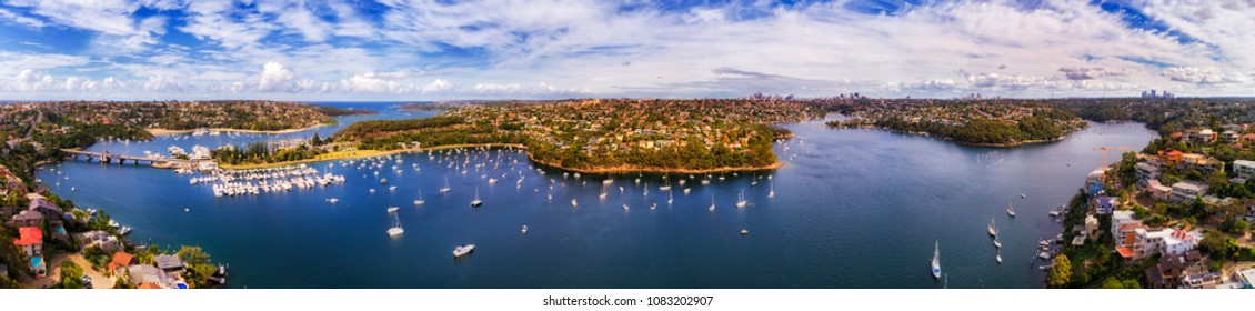 Middle harbour of Sydney - wide aerial panorama from Spit Bridge to Mosman and lower north shore suburbs with distant CBD suburbs on the horizon.