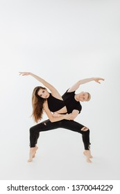 Middle Level Turnout Caucasian Dance Couple Pose. Beautiful Dancer Wear Black Denim and Top Balance on Toe Isolated on White Background. Man and Woman Contemporary Perfomer Looking at Camera