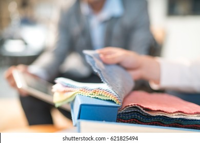 The middle of the male designer walking through the fabric samples in the studio.