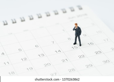 Middle of month for salary man, timeline or schedule concept, miniature people businessman office guy standing at 15th on calendar, looking at the goal or target to launch the project date.