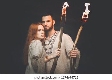 middle plan: a bearded guy and a red-haired girl in Slavic clothes and handmade ornaments hold in their hands torches lit up and look at the frame