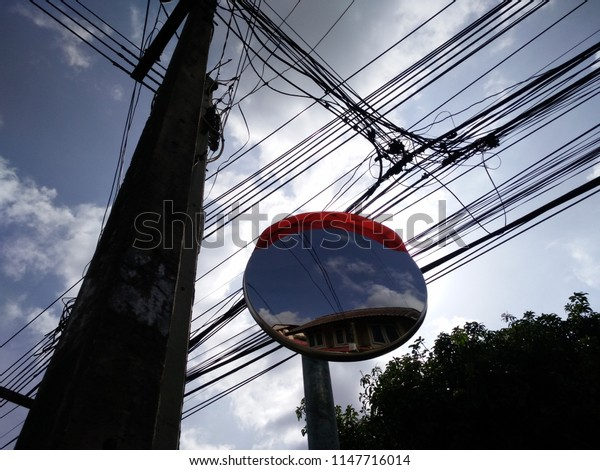 In a middle of the road in thailand, there are always confused electricity wires around. With an wide-angle lens mirror.