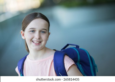 middle school girl in a pink shirt with a purple backpack