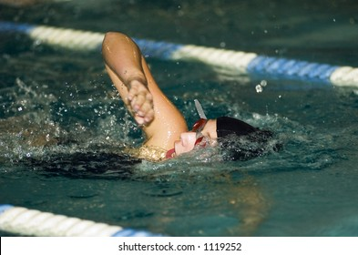 A middle school swimmer competes in a freestyle race.