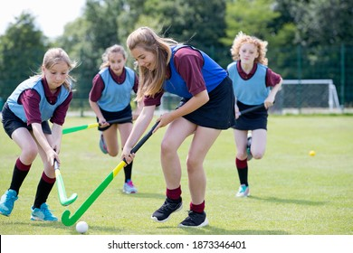 Middle schoolgirls playing hockey on the field in physical education class