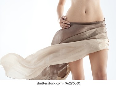 Middle section of a woman's body wearing a silk skirt around her heaps.