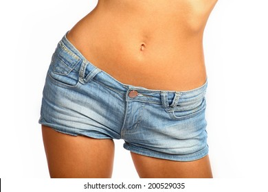 Middle section of a young and fit woman with short denim pants. Woman in jeans texas shorts