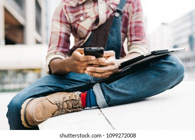 middle section young handsome black man millennial using smart phone and tablet - technolofy, social network, remote working concept