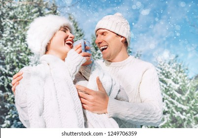 Middle shot of happy cheerful sincerely laughing caucasian couple dressed knitted outfit clothes in the snowy winter forest. Sincerely young couple relations concept.
