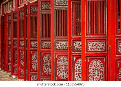A middle shot of row of red doors in the purple forbidden city in Vietnam