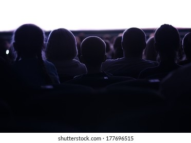 Middle shot of sihouettes of people from back watching cinema or performance with white empty space