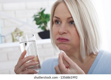 Middle woman hold glass still water and pill. Sick woman taking putting pill in mouth painkiller or antibiotic medicine, depression treatment chronic disease or biologically active supplement concept