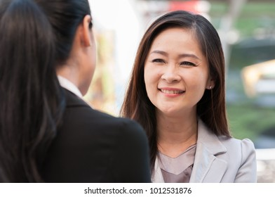 Middle and young Asian business people greeting and smiling in morning, friendship happy conversation.