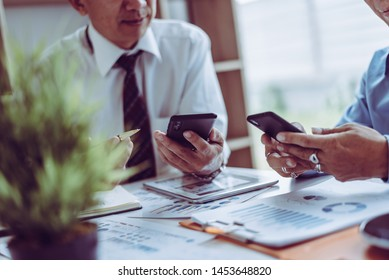 Middle-age Asian two business managers crew working with new startup project while sitting in coffee shop modern office.