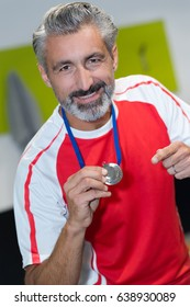 middle-age athlete competitor showing his winning medal