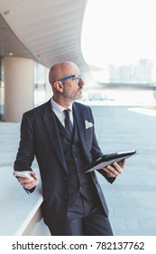 Middle-age contemporary businessman outdoor in the city, using smart phone and tablet hand hold - business, work, communication concept