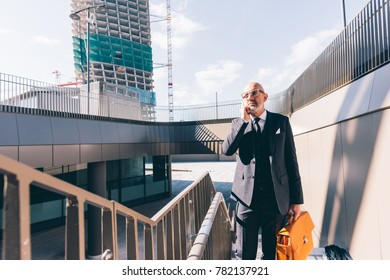 Middle-age contemporary businessman outdoor in the city walking talking smart phone- communicati