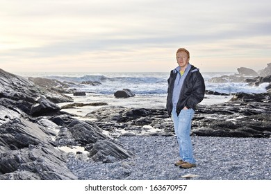 A middle-age male stands on a rocky beach in the winter at Botanical Beach, Port Renfrew, BC, Canada as the sun is low in the sky and the high tide is nearing.