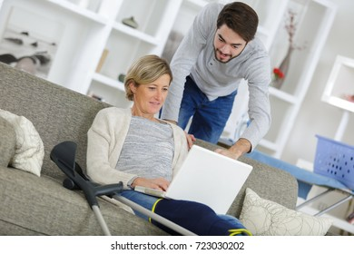 middle-age woman injured sitting on the sofa and using laptop
