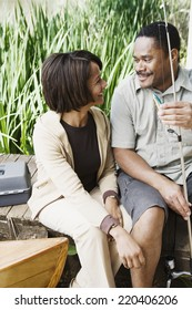 Middle-aged African couple smiling with fishing gear