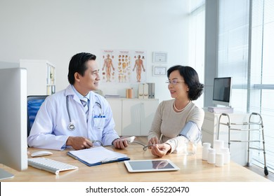 Middle-aged Asian doctor measuring blood pressure of smiling senior woman and taking necessary notes in medical record