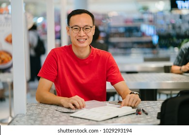 A middle-aged Asian man (Chinese or Japanese) is writing in his journal notebook at a cafe.