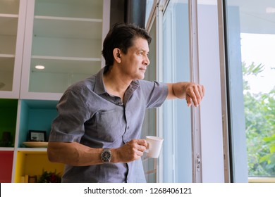 Middle-aged Asian man looking through a window, sipping coffee and using ideas