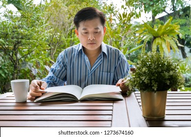 A middle-aged Asian man reading a book resting in the backyard