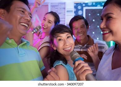 Middle-aged Asian people having fun in karaoke