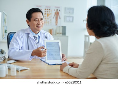 Middle-aged Asian physician looking at female patient with smile while pointing at screen of digital tablet, waist-up portrait