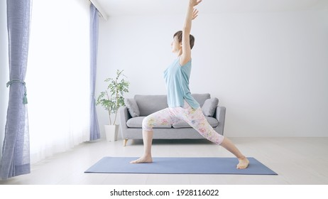 Middle-aged Asian woman doing yoga in room.