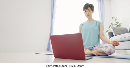 Middle-aged Asian woman taking online yoga. Mindfulness.