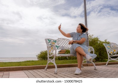 A middle-aged Asian woman taking a selfie while sitting on a bench by the sea