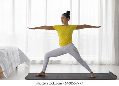 Middle-aged Asian woman wearing sportswear practice yoga on the mat. (Warrior Pose) Standing on both arms One leg bent over the knee to the front The other leg stand straight. Bedroom background