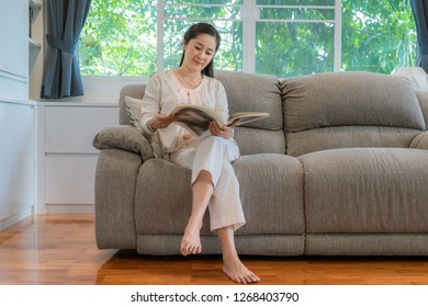 Middle-aged Asian women are reading books, relaxing in the  living room.