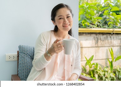 Middle-aged Asian women sit and sip coffee in the backyard.