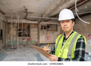 A middle-aged Asian worker checking something with a checklist in his hand.
