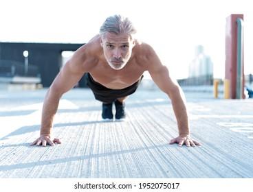 Athletiker mittleren Alters, der im Freien Liegestütze macht. Fitness und Sport im Freien städtische Umgebung.