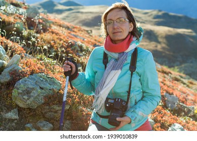 Middle-aged attractive woman mountain portrait. Healthy lifestyle. Beautiful female person. Trekking of mature woman with dslr camera. Solo tourist  in the Alps.  Scenic summer photo