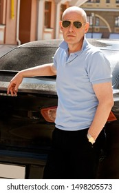 Middle-aged bald man in sunglasses and blue T-shirt standing near his black car. He is businessman.