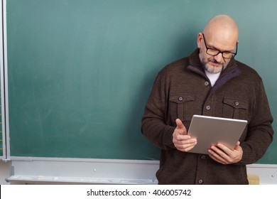 Middle-aged balding male teacher wearing glasses standing reading on a tablet computer in front of a blank chalkboard with copy space