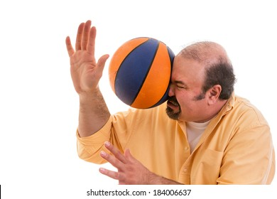 Middle-aged balding man with a goatee playing sport being hit by a Illinois basket ball with force in the face when he misses a catch or as an unexpected accident to a spectator, on white.