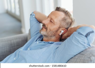 Middle-aged bearded man enjoying music in wireless earbuds, while laying back on the sofa with his hands behind his nape and eyes closed