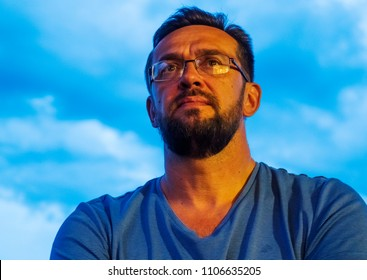 Middle-aged bearded man with glasses against the sky portrait