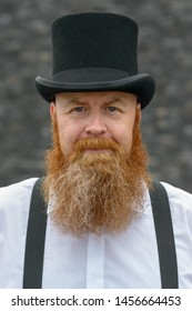 Middle-aged bearded man in top hat and braces looking at the camera with a quiet friendly smile over a grey background