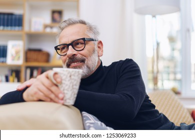 Middle-aged bearded man wearing glasses relaxing in his living room leaning over the back of the sofa holding a mug of coffee